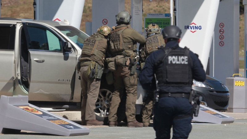 RCMP officers prepare to take a person into custody at a gas station in Enfield, N.S. on Sunday April 19, 2020. THE CANADIAN PRESS/Tim Krochak