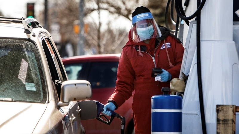 A Domo employee wears full PPE for protection as he fills up cars during the COVID-19 Pandemic, in Edmonton, Alta., on Saturday, April 18, 2020. THE CANADIAN PRESS/Jason Franson