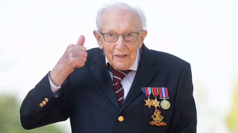 99-year-old war veteran Captain Tom Moore poses for a photo at his home in Marston Moretaine, England, after he achieved his goal of 100 laps of his garden, raising millions of pounds for the NHS with donations to his fundraising challenge from around the world, Thursday April 16, 2020. (Joe Giddens/PA via AP)
