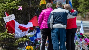 A family pays their respects to victims of the mass killings at a checkpoint on Portapique Road in Portapique, N.S. on Friday, April 24, 2020. (THE CANADIAN PRESS/Andrew Vaughan)