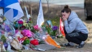 A woman pays her respects at a roadside memorial on Portapique Road in Portapique, N.S. on Friday, April 24, 2020. (THE CANADIAN PRESS/Andrew Vaughan)