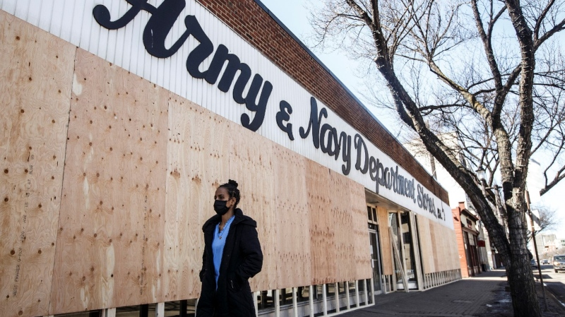 A pedestrian walks past long time business, Army and Navy Department Store as it gets boarded up and closes itÕs doors, during the COVID-19 Pandemic, in Edmonton Alta, on Thursday April 16, 2020. THE CANADIAN PRESS/Jason Franson