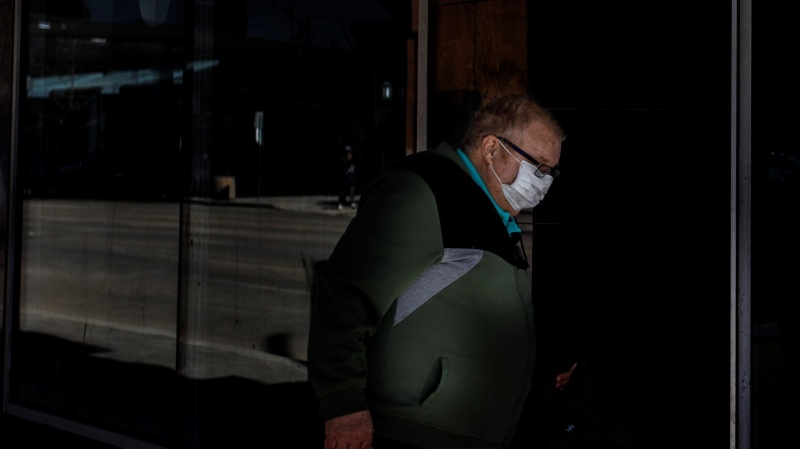 A person walks through a spot of light while wearing a mask to help the stop of COVID-19 during the world pandemic, in Edmonton Alta, on Wednesday April 8, 2020. THE CANADIAN PRESS/Jason Franson