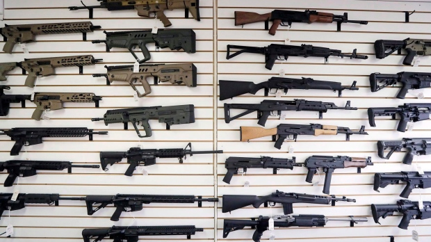 In this Oct. 2, 2018, semi-automatic rifles fill a wall at a gun shop in Lynnwood, Wash. Starting Tuesday, Jan. 1, 2019. The federal government is poised to ban a variety of assault-style rifles. THE CANADIAN PRESS/AP-Elaine Thompson