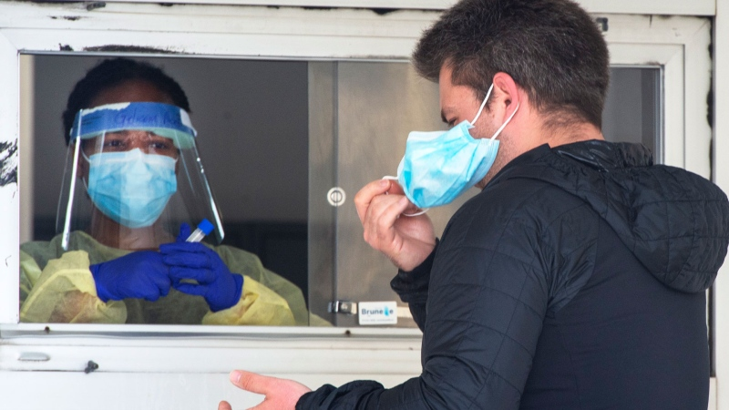 A man removes his face mask before being tested at a COVID-19 testing clinic Friday, May 1, 2020 in Montreal North. The area has been identified as one of the hardest hit with COVID-19 on the island. THE CANADIAN PRESS/Ryan Remiorz