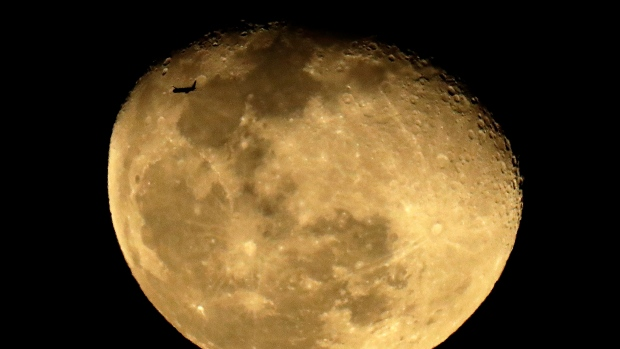 A passenger jet passes the waning moon after taking off from Phoenix Sky Harbor International Airport, Tuesday, Feb. 11, 2020, in Phoenix. (AP Photo/Charlie Riedel)