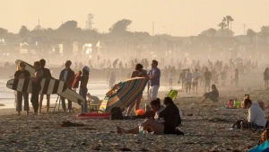 Beachgoers spread out the day before the beach is scheduled to close during the coronavirus outbreak, Thursday, April 30, 2020, in Newport Beach, Calif. California Gov. Gavin Newsom on Thursday temporarily closed Orange County's coastline after large crowds were seen there. (AP Photo/Mark J. Terrill)