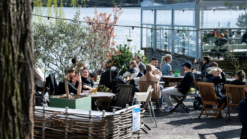 People drink and eat at an outdoor restaurant in Stockholm, Sweden, Sunday, April 26, 2020, amid the coronavirus pandemic. Sweden has kept large parts of society open for normal life to continue while observing some advice, although this has also attracted criticism. (Jessica Gow/TT News Agency via AP)