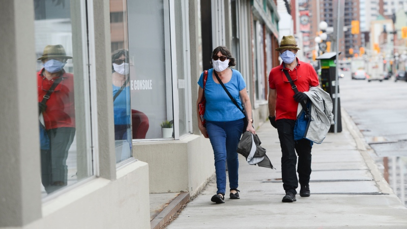 A couple wear masks while out for a walk in downtown Ottawa during the COVID-19 pandemic on Friday, May 1, 2020. THE CANADIAN PRESS/Sean Kilpatrick
