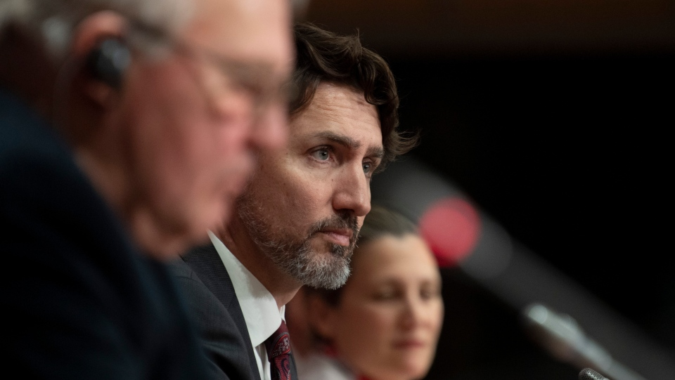 Prime Minister Justin Trudeau, centre, is seen during an announcement fon a ban on military style assault weapons during a news conference in Ottawa, Friday May 1, 2020. THE CANADIAN PRESS/Adrian Wyld