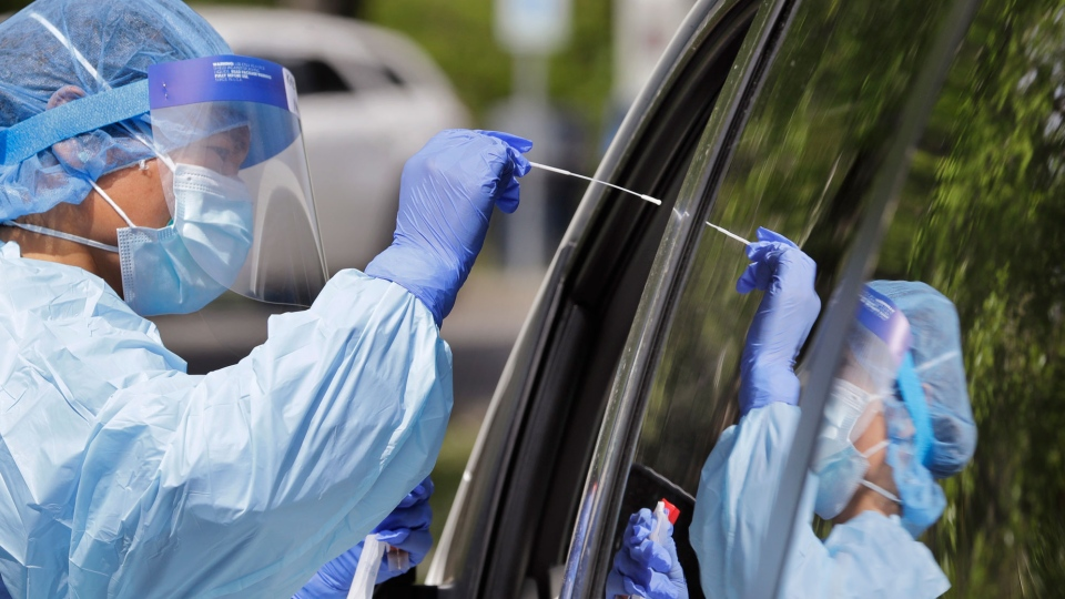 Medical assistant Melanie Zamudio is reflected in the window of a car as she reaches in to take a nasal swab from a driver at a drive-up coronavirus testing site. (Elaine Thompson/AP)