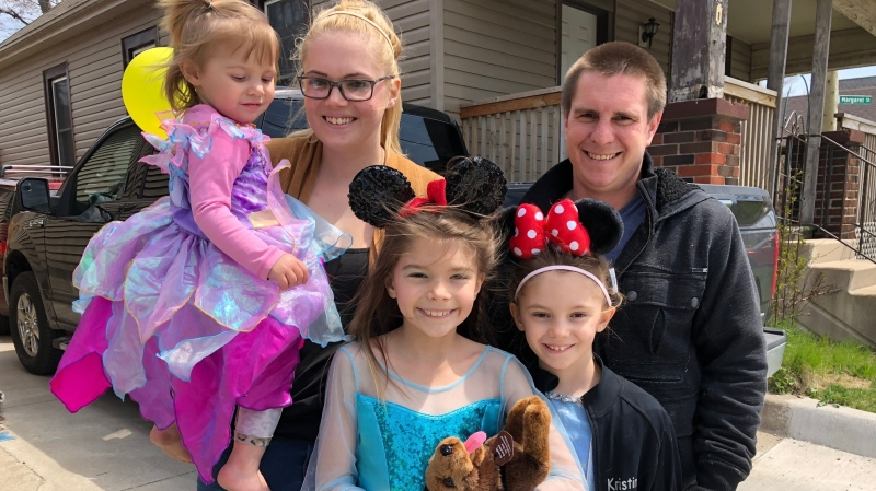Cloey Prince (middle) with her parents and sisters as the community holds a surprise Disney parade in her honour. (Jordyn Read / CTV News)