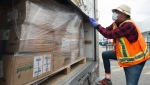 A driver for Safecare B.C. secures a load of personal protective equipment in a truck for Safecare B.C. in Surrey, B.C. Tuesday, April 28, 2020. (THE CANADIAN PRESS / Jonathan Hayward)