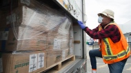 In this file photo, a driver for Safecare B.C. secures a load of personal protective equipment in a truck for Safecare B.C. in Surrey, B.C. Tuesday, April 28, 2020. (THE CANADIAN PRESS / Jonathan Hayward)