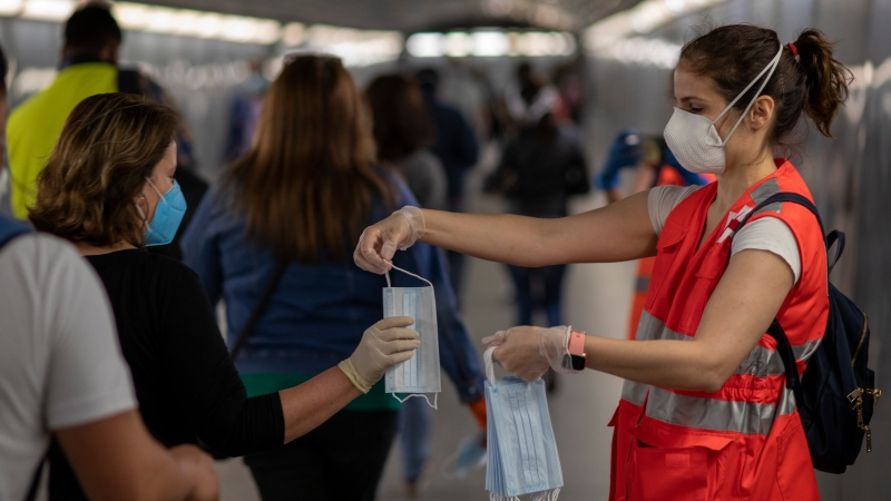 Commuters receive face masks distributed by Red Cross volunteers in a train station in Barcelona, Spain, Monday, May 4, 2020. Spaniards will be able to get a haircut, buy glasses or take away food as long as they have previously made an appointment and they travel on public transport with mouth and nose covered with mandatory masks. The country enters the first stage of its 4-phase lockdown rollback helped by the lowest daily reports of deaths from coronavirus in 1.5 months. (AP Photo/Emilio Morenatti)