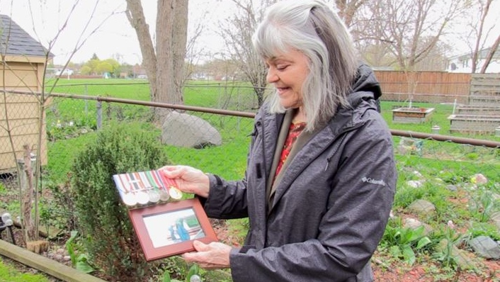 Marilyn Reid holding a photo of her late husband John and his military medals on May 4, 2020. (Celine Zadorsky/CTV London)