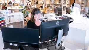 A receptionist wears a visor at a furniture store in St-Jean-sur-Richelieu, Que. on Monday, May 4, 2020. Retail stores outside the greater Montreal area have been allowed to reopen after weeks of forced closure due to the COVID-19 pandemic. THE CANADIAN PRESS/Paul Chiasson