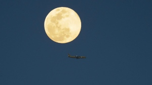 An airplane flys past a supermoon as it rises in the sky Tuesday, April 7, 2020, in Orlando, Fla. (AP Photo/John Raoux)