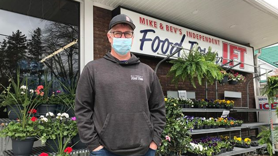 A man with a masks stands outside a grocery store