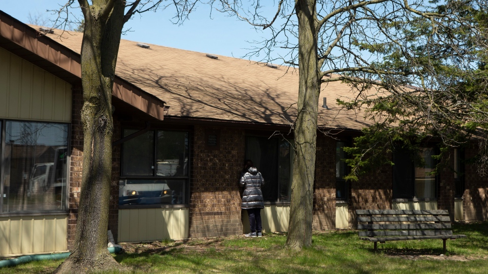 A woman tries to speak to a relative through a window at Orchard Villa Care home, in Pickering, Ont. on Saturday, April 25, 2020. The care home has had over half it's residents test positive for COVID-19. THE CANADIAN PRESS/Chris Young