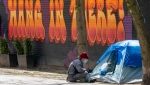 A nurse sits outside a tent at an encampment outside Sanctuary Ministries in Toronto on Monday, May 4, 2020. THE CANADIAN PRESS/Frank Gunn