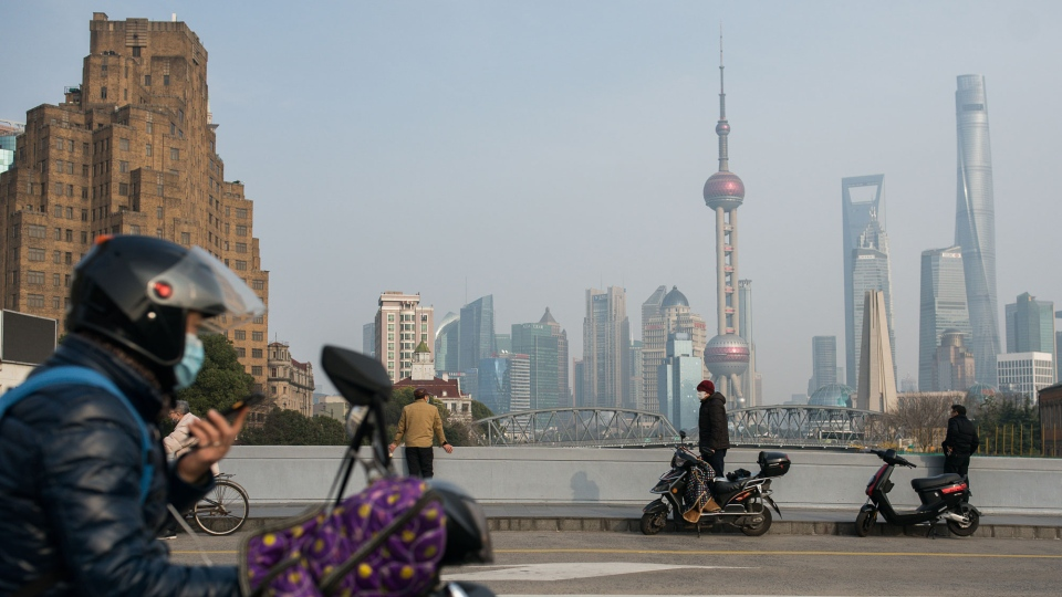 Pedestrians and bikers wear protective masks on a bridge over Suzhou River near the Bund on March 11, 2020 in Shanghai, China. (Yifan Ding/Getty Images)