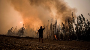 Verne Tom photographs a wildfire burning approximately 20 kilometres southwest of Fort St. James, B.C., on Wednesday, Aug. 15, 2018. (Darryl Dyck / THE CANADIAN PRESS)