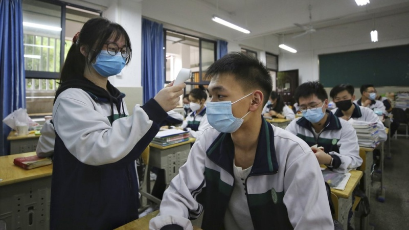 A student wearing a protective face mask to help curb the spread of the new coronavirus checks temperature of her classmates at a high school in Wuhan in central China's Hubei province, Wednesday, May 6, 2020. (Chinatopix via AP)
