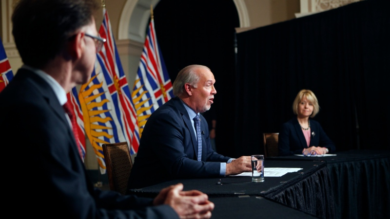 Premier John Horgan is joined by Provincial Health Officer Dr. Bonnie Henry and Health Minister Adrian Dix as they discuss reopening the province's economy in phases in response to the COVID-19 pandemic during a press conference in the rotunda at Legislature in Victoria, B.C., on Wednesday May 6, 2020. THE CANADIAN PRESS/Chad Hipolito