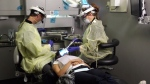 Two dentists in personal protective equipment (PPE) help a patient in this image.