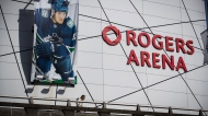 A woman walks past a large photo of Vancouver Canucks captain Bo Horvat outside Rogers Arena, home to the NHL team, in Vancouver, on Thursday, March 12, 2020. THE CANADIAN PRESS/Darryl Dyck
