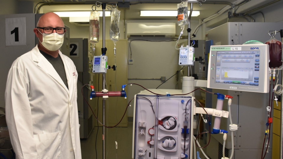 Dr. Chris McIntyre stands with one of the modified dialysis machines being used for the new COVID-19 treatment at LHSC in London, Ont.