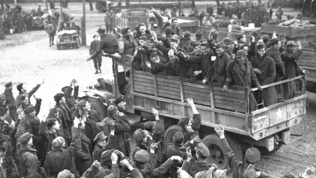 British prisoners of war, foreground, bid farewell to fellow prisoners of war, a group of U.S. GIs, as the first U.S. truck leaves for Allied lines, at a camp at Altengrabow, Germany, May 7, 1945. (AP Photo/Henry L. Griffin)
