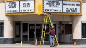 Two men work on the marquee of an independent theatre in Ottawa, Wednesday, May 6, 2020. (Adrian Wyld/THE CANADIAN PRESS)