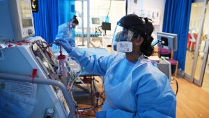 A member of the clinical staff wearing Personal Protective Equipment PPE cares for a patient with coronavirus in the intensive care unit at the Royal Papworth Hospital in Cambridge, England, Tuesday May 5, 2020. (Neil Hall / Pool via AP)