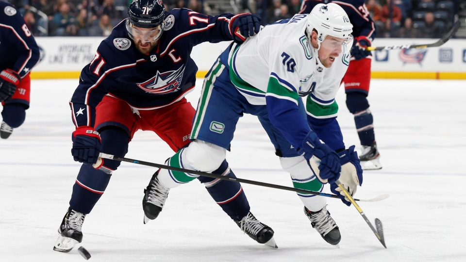 Columbus Blue Jackets' Nick Foligno, left, pushes Vancouver Canucks' Tanner Pearson away from the puck during the first period of an NHL hockey game Sunday, March 1, 2020, in Columbus, Ohio. (AP  / Jay LaPrete)