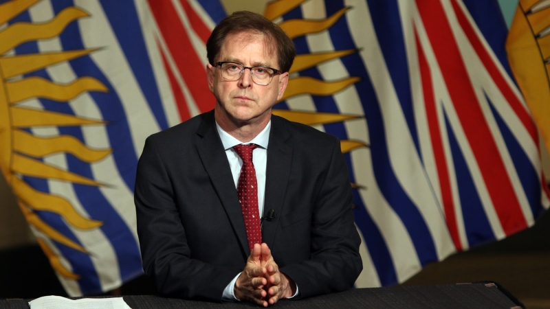 Health Minister Adrian Dix looks on as Premier John Horgan discusses reopening the province's economy in phases in response to the COVID-19 pandemic during a press conference in the rotunda at Legislature in Victoria, B.C., in May 2020. THE CANADIAN PRESS/Chad Hipolito