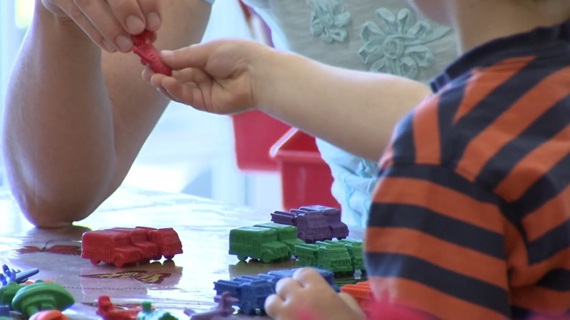 Child and educator play at daycare centre (file)