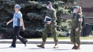 A staff member escorts members of the Canadian Armed Forces in to Orchard Villa Care home, in Pickering, Ont. on Saturday, April 25, 2020. The care home has had over half it's residents test positive for COVID-19. THE CANADIAN PRESS/Chris Young