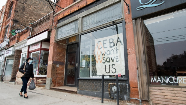 A closed store front boutique business called Francis Watson pleads for help displaying a sign in Toronto on Thursday, April 16, 2020. (Nathan Denette/The Canadian Press)