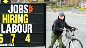 A woman checks out a jobs advertisement sign during the COVID-19 pandemic in Toronto on Wednesday, April 29, 2020. Students are starting to look for summer work, with few options in the usual places. THE CANADIAN PRESS/Nathan Denette