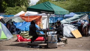 People sit together at a table at a homeless camp at Oppenheimer Park, in the Downtown Eastside of Vancouver, on Wednesday, May 6, 2020. (Darryl Dyck / THE CANADIAN PRESS)