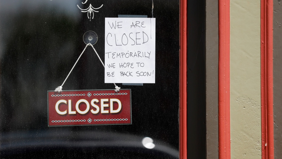 A sign hangs in the window of a popular sandwich shop that has temporarily closed due to the coronavirus Friday, May 1, 2020, in St. Louis. Business in some parts of Missouri will be allowed to reopen on Monday after the state's stay-at-home order expires while others in St. Louis will remain closed as restrictions in the city remain in place. (AP Photo/Jeff Roberson)