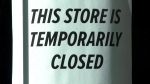 A closed sign is seen in a store window in this file photo.