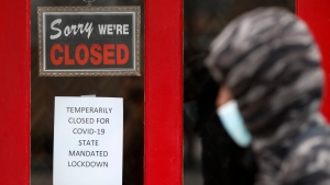 FILE - In this May 7, 2020 file photo, a pedestrian walks by The Framing Gallery, closed due to the COVID-19 pandemic, in Grosse Pointe, Mich. The U.S. unemployment rate hit 14.7% in April, the highest rate since the Great Depression, as 20.5 million jobs vanished in the worst monthly loss on record. The figures are stark evidence of the damage the coronavirus has done to a now-shattered economy.. (AP Photo/Paul Sancya, File)