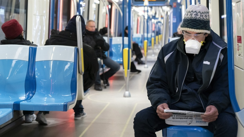 Commuters keep their distances in a subway train in Montreal, on Wednesday, April 22, 2020. ontreal's transit authority is strongly recommending that passengers wear a mask when riding the bus or subway. THE CANADIAN PRESS/Paul Chiasson