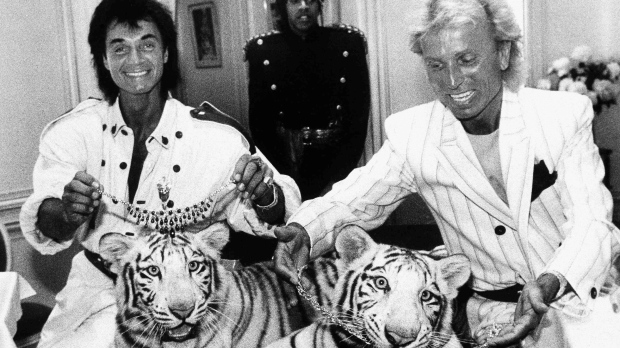 In this June 4, 1987, file photo, Las Vegas magicians Roy Horn, left, and Siegfried Fischbacher pose in New York, with their rare white tigers, Neva, left, a female, and Vegas, a male, during a stop at Van Cleef & Arpels jewelry before their departure for Germany. (AP Photo/Scott McKiernan, File)