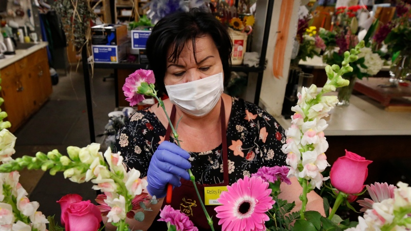Olga Karamalak puts the finishing touches on a Mother's Day flower arraignment at Relles Florist in Sacramento, Calif., on May 5, 2020. THE CANADIAN PRESS/AP - Rich Pedroncelli