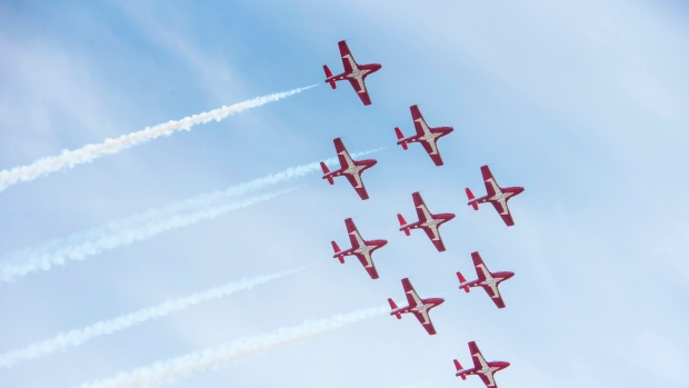 The Canadian Forces Snowbirds fly in the team's signature nine-jet formation, with trailing white smoke, over Fredericton, on Sunday,May 3, 2020.  THE CANADIAN PRESS/Stephen MacGillivray