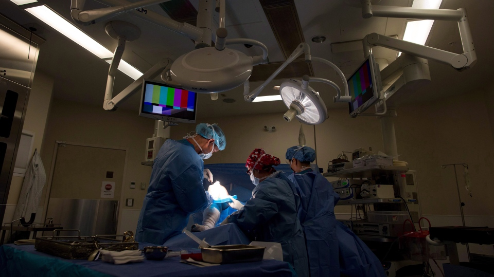 Dr. Darius Viskontas, left, prepares to remove a cyst from a male patient's knee, with assistance from Dr. Anne Wachsmuth, centre, and Miwa Holm, an operating room registered nurse, at the Cambie Surgery Centre, in Vancouver on Wednesday, August 31, 2016. Dr. Brian Day, a self-styled champion of privatized health care, is bringing his fight to British Columbia Supreme Court on Tuesday for the start of a months-long trial he says is about patients' access to affordable treatment, while his opponents accuse him of trying to gut the core of Canada's medical system. THE CANADIAN PRESS/Darryl Dyck
